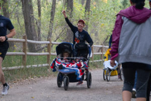 Women pumps her fist as she pushes a stroller during the Homecoming 5K