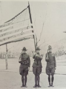 A black and white photo of three male Mines ROTC members present the colors in 1925.